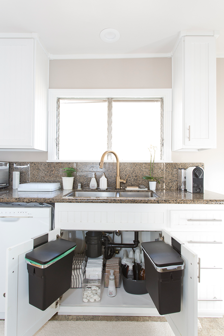 Decluttering and organizing the kitchen sink area and cabinets with